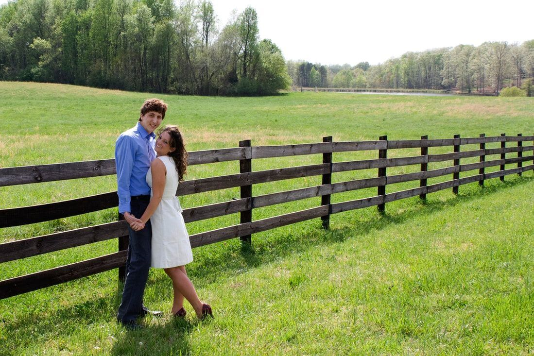 Engaged couple standing by wooden fence