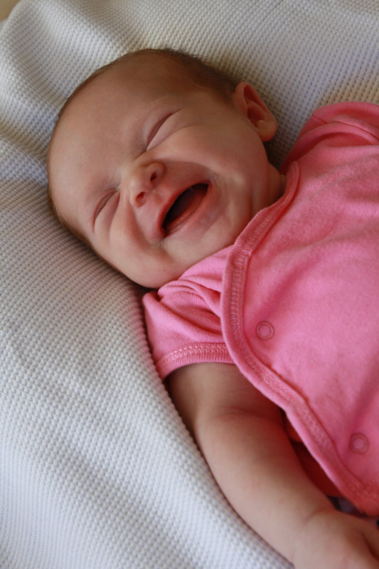 Baby in pink laughing