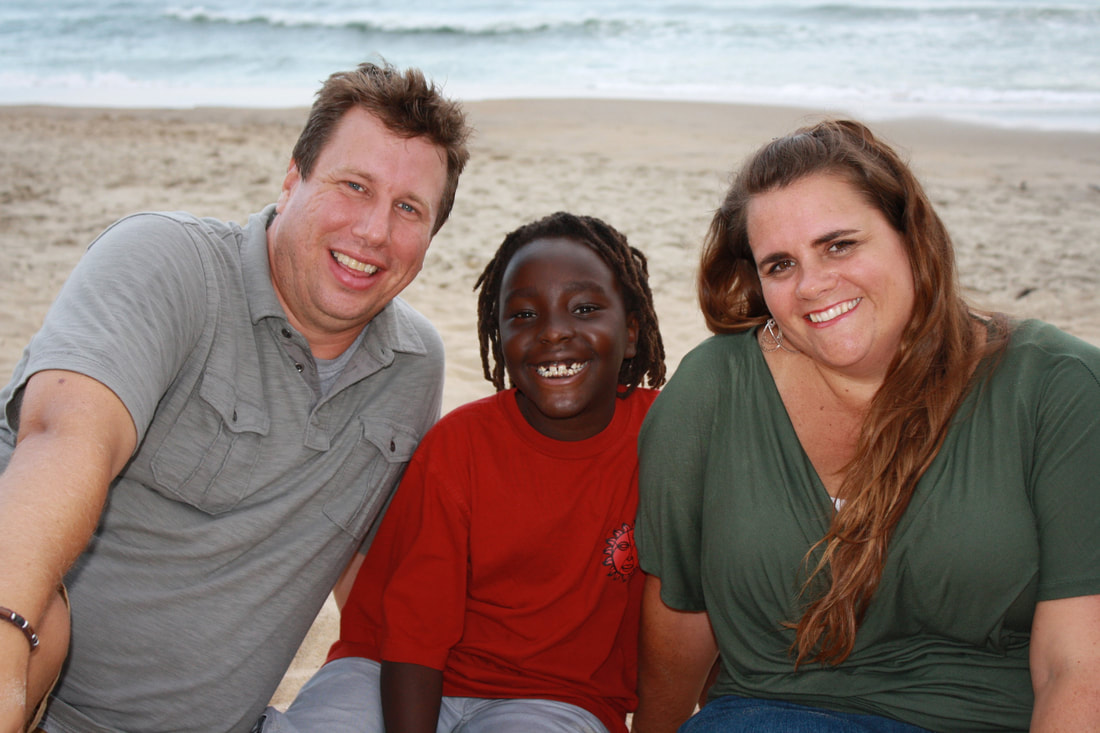 family of three portrait on the beach