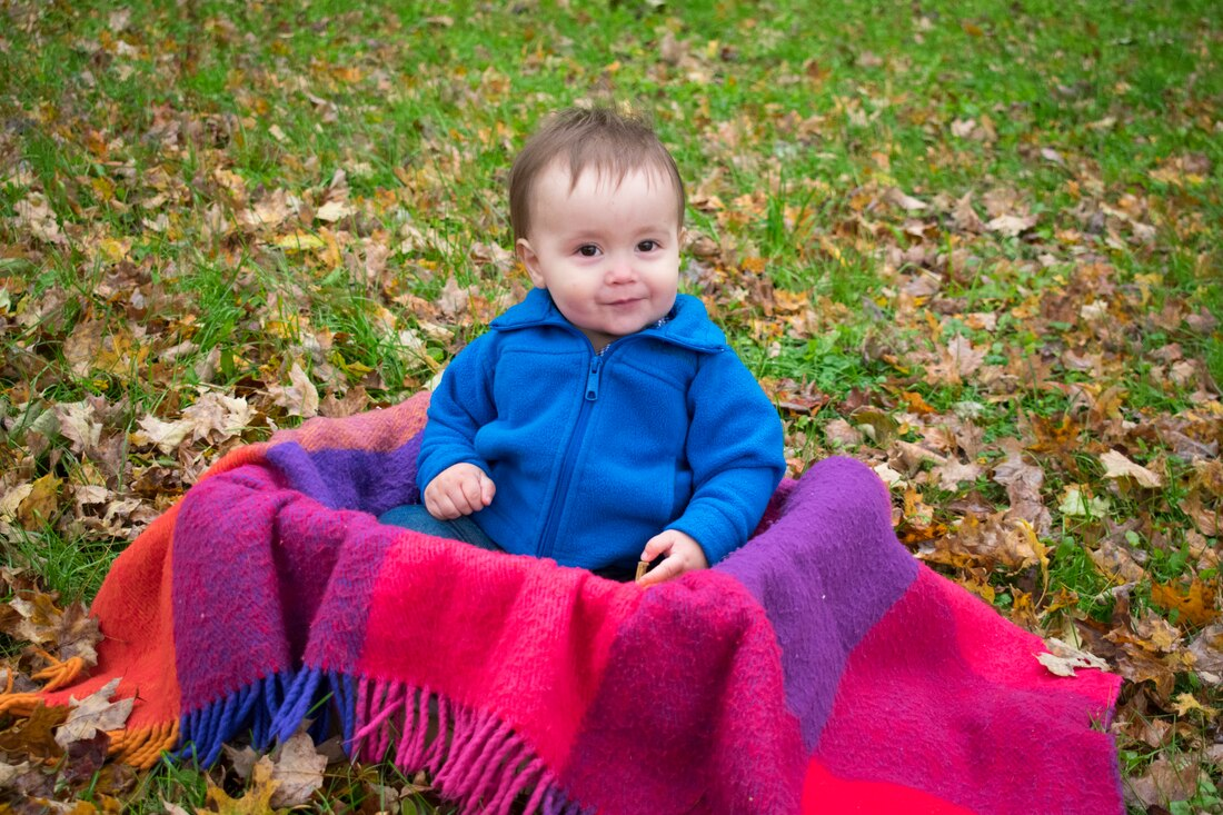 toddler smiling sitting outside in a box with a blanket